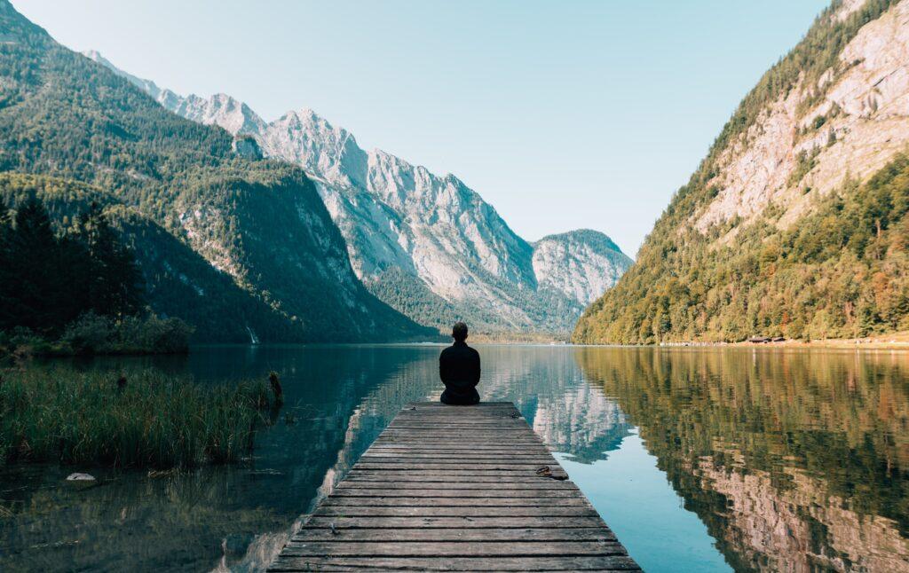 mujer en un lago sentada en un porche de madera